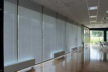 Spacius room with wooden blinds, sunrays coming through